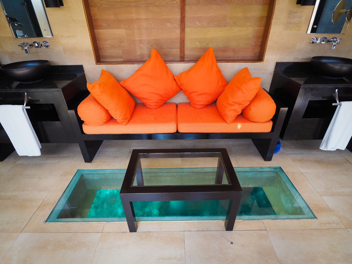 Sofa in the Adaaran Prestige Vadoo Bathroom with a glass floor to see the fish